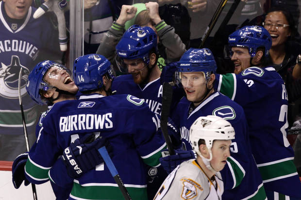   Vancouver Canucks&#039; Lee Sweatt, left, celebrates after scoring his first NHL goal with teammates, ffrom left of Sweatt, Alex Burrows, Daniel Sedin, of Sweden, Christian Ehrhoff, of Germany, and Henrik Sedin, of Sweden, as Nashville Predators&#039; Jerred Smithson, lower right, skates past during the third period of an NHL hockey game in Vancouver, British Columbia, Wednesday Jan. 26, 2011. (AP Photo/THE CANADIAN PRESS/Darryl Dyck)  