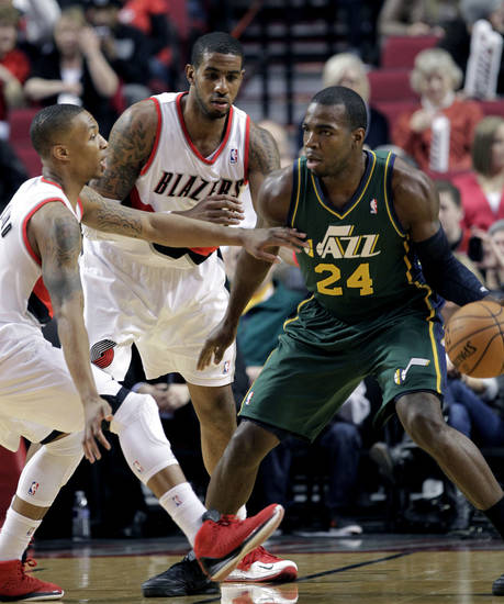 Utah Jazz forward Paul Milsap, right, is double-teamed by Portland Trail Blazer guard Damian Lillard, left, and forward LaMarcus Aldridge during the first quarter of an NBA basketball game in Portland, Ore., Saturday, Feb. 2, 2013. (AP Photo/Don Ryan)