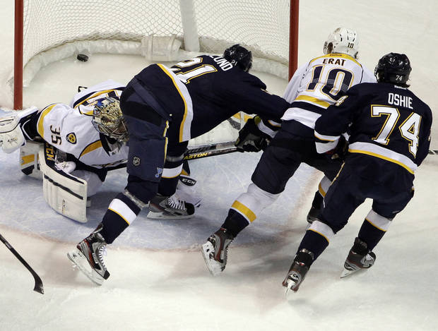 St. Louis Blues' T.J. Oshie, right, scores past Nashville Predators goalie Pekka Rinne, left, of Finland, as the Blues' Patrik Berglund (21), of Sweden, and Predators' Martin Erat (10), of the Czech Republic, look on during the first period of an NHL hockey game on Thursday, Jan. 24, 2013, in St. Louis. (AP Photo/Jeff Roberson)
