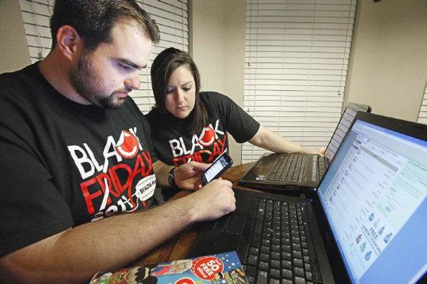 Husband-and-wife team Travis and Rachel Benham, of Mustang, go over their Black Friday shopping list. PHOTO BY DAVID MCDANIEL, THE OKLAHOMAN