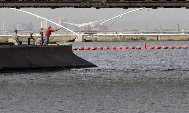 A fisherman casts his line into the Tempe Town Lake, Monday, Nov. 26, 2012 in Tempe, Ariz. With cactus and strip malls obstructing the view at times, visitors could easily write Phoenix off as a place where water and culture are scarce. But this metropolis _ which includes upscale Scottsdale and college town Tempe _ is a nature lover's oasis with pristine peaks and vast Sonoran desert. (AP Photo/Matt York)