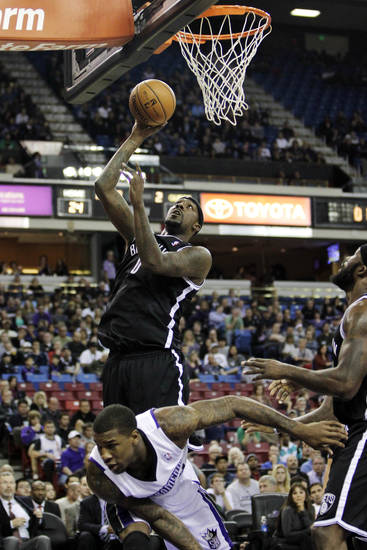 Brooklyn Nets forward Andray Blatche, top left, shoots over Sacramento Kings' Thomas Robinson during the first quarter of an NBA basketball game in Sacramento, Calif., Sunday, Nov. 18, 2012. (AP Photo/Rich Pedroncelli)