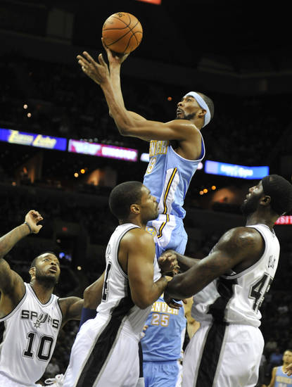 Denver Nuggets forward Corey Brewer, top, shoots over San Antonio Spurs', from left, Josh Powell, Gary Neal and DeJuan Blair during the first half of an NBA preseason basketball game on Friday, Oct. 12, 2012, in San Antonio. (AP Photo/Bahram Mark Sobhani)