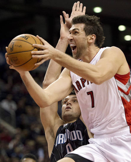 Toronto Raptors forward Andrea Bargnani, right, drives to the basket against Orlando Magic forward Nikola Vucevic during the first half of an NBA basketball game in Toronto, Sunday, Nov. 18, 2012. (AP Photo/The Canadian Press, Frank Gunn)