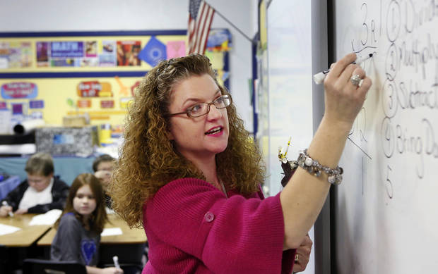 Sallie Harrison, a fourth-grade science and math teacher at Meeker Elementary School gives a lesson in long division. Harrison has has multiple sclerosis.    Photo by Jim Beckel, The Oklahoman <strong>Jim Beckel - THE OKLAHOMAN</strong>