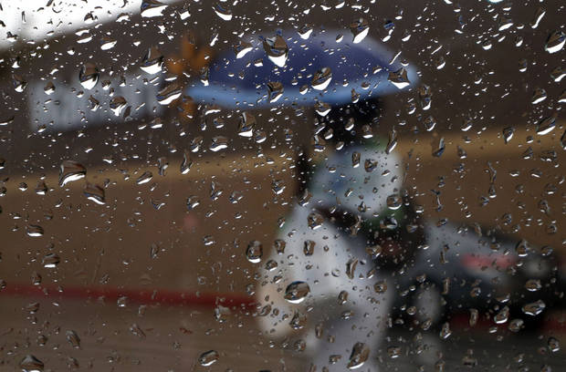 A shopper is pictured through a water drops on a window, Saturday, Aug. 18, 2012. Photo by Sarah Phipps, The Oklahoman