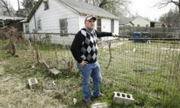 Mike Harrell, who shot the pit bull that attacked two women Tuesday, stands outside the fence that he kept between him and the dog.