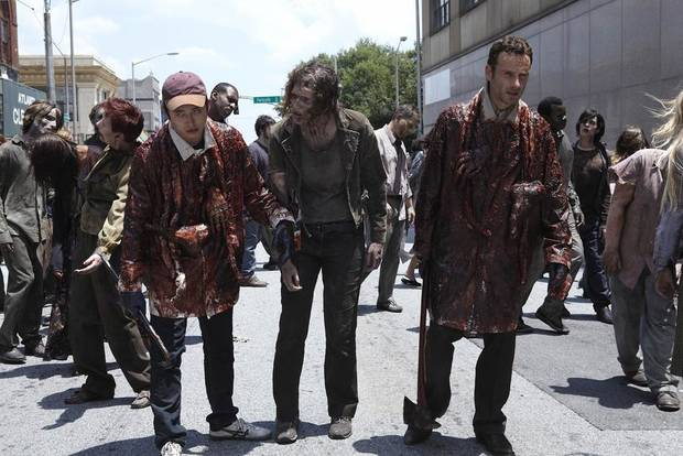 "Steven Yeun, left, and Andrew Lincoln, right, try to blend in with the zombie population in a scene from ""The Walking Dead."" (AP Photo/AMC)"