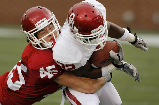 Caleb Gastelum (45) tackles Roy Finch (22) after a pass completion during the University of Oklahoma (OU) football team's annual Red and White Game at Gaylord Family/Oklahoma Memorial Stadium on Saturday, April 14, 2012, in Norman, Okla.  Photo by Steve Sisney, The Oklahoman