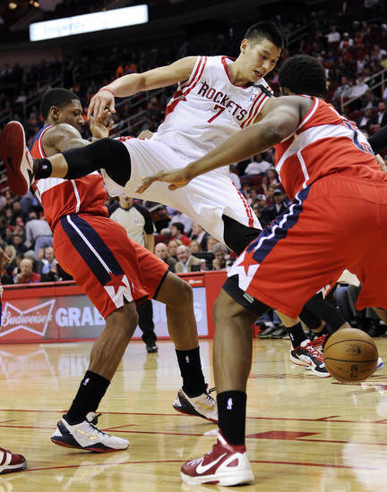 Houston Rockets' Jeremy Lin (7) loses the ball between Washington Wizards' Bradley Beal, left, and Kevin Seraphin in the second half of an NBA basketball game, Wednesday, Dec. 12, 2012, in Houston. The Rockets won 99-93. (AP Photo/Pat Sullivan)