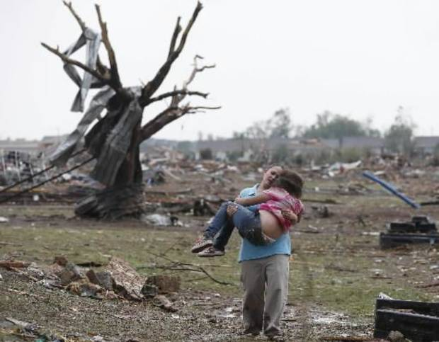 """In this May 20, 2013 file photo, LaTisha Garcia carries her 8-year-old daughter, Jazmin Rodriguez near Plaza Towers Elementary School after a massive tornado carved its way through Moore, Okla., leaving little of the school and neighborhood. This picture, published on hundreds of front pages around the world, has become one of the enduring images from the storm. It is featured in the photo exhibit """"Not Just Another Day in May."""" (AP Photo/Sue Ogrocki)"""