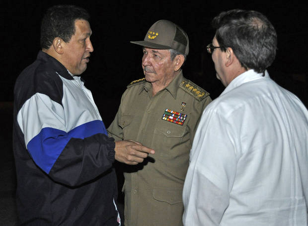 In this picture released by Cuba's state newspaper Granma, Venezuela's President Hugo Chavez, left, speaks to Cuba's President Raul Castro, center, before the South American leader departs for Venezuela from the Jose Marti airport in Havana, Cuba, Friday, Dec. 7, 2012. Chavez returned home to Caracas early Friday after 10 days of medical treatment in Cuba. (AP Photo/Granma)