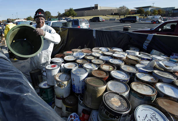 Michael Holmes loads paint cans on a truck for safe disposal Saturday in Norman.