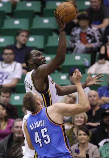 Utah Jazz center Al Jefferson, top, goes to the basket as Oklahoma City Thunder center Cole Aldrich (45) looks on in the first quarter during an preseason NBA basketball game on Friday, Oct. 12, 2012, in Salt Lake City. (AP Photo/Rick Bowmer) ORG XMIT: UTRB104