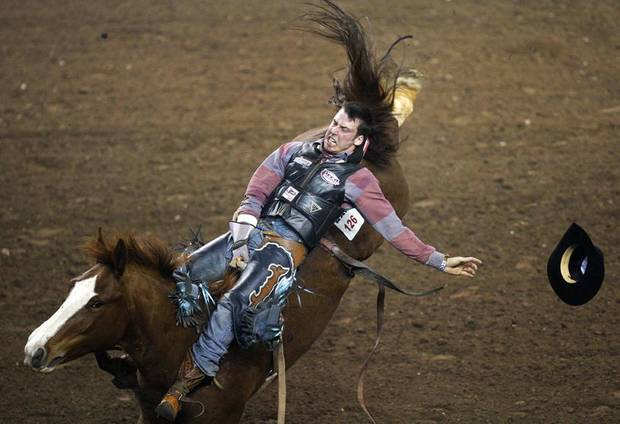 Justin Miller of Billings, Montana, loses his hat as he rides Will He Lounge or Not for a score of 75 in the bareback riding event during the PRCA Dodge National Circuit Finals Rodeo at State Fair Arena, Saturday afternoon, April 2, 2011. Photo by Nate Billings, The Oklahoman ORG XMIT: KOD