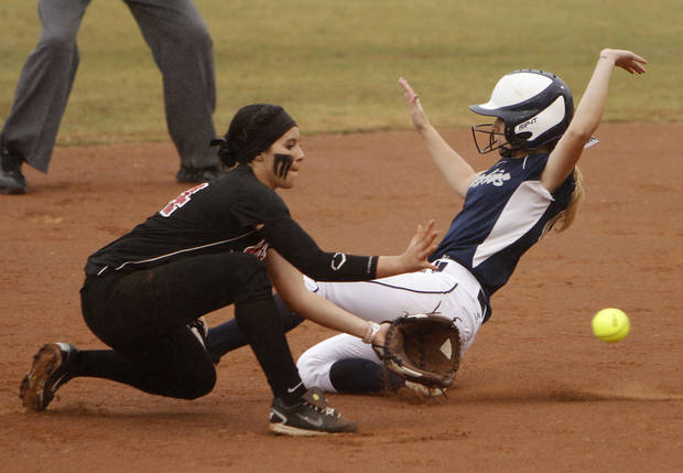 Edmond North's Sheridan Bond (00) slides past Yukon's Jasmine Holman (14) during a 6A state softball semifinals game between Edmond North and Yukon at ASA Hall of Fame Stadium in Oklahoma City, Okla., Friday, Oct. 12, 2012.  Photo by Garett Fisbeck, The Oklahoman