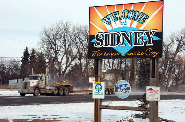 This Feb. 28, 2012 photo shows a truck driving by the welcome sign for Sidney, Mont. Sidney is experiencing a boom spurred by companies seeking to extract oil from the massive Bakken formation beneath western North Dakota and eastern Montana. More than 16 million barrels of crude are now being pumped every month from the massive Bakken oil field beneath eastern Montana. But Sidney's new-found prosperity doesn't dull the sting of the recent kidnapping and apparent murder of a local teacher, Sherry Arnold, who authorities allege was snatched from a Sidney street by two men among the thousands in search of their own slice of the boom's multi-billion-dollar payoff. (AP Photo/Matthew Brown)