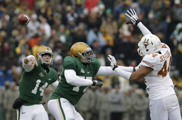 Baylor quarterback Bryce Petty (14) passes as offensive linesman Kelvin Palmer (77) blocks Texas defensive end Jackson Jeffcoat (44) during the first half of an NCAA college football game on Saturday, Dec. 7, 2013, in Waco, Texas. (AP Photo/LM Otero)
