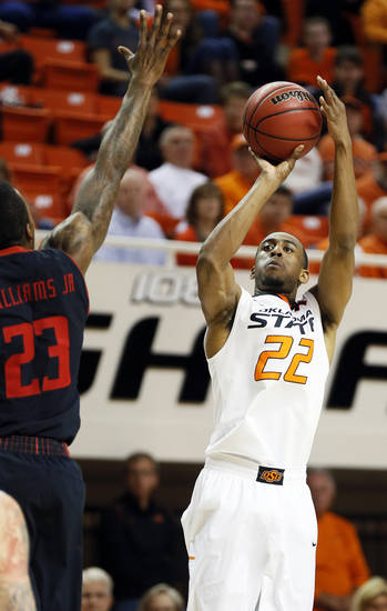 Oklahoma State's Markel Brown (22) shoots against Texas Tech's Jamal Williams Jr. (23) during a men's college basketball game between Oklahoma State University (OSU) and Texas Tech at Gallagher-Iba Arena in Stillwater, Okla., Saturday, Jan. 19, 2013.  Photo by Nate Billings, The Oklahoman