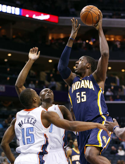 Indiana Pacers' Roy Hibbert (55) shoots over Charlotte Bobcats' Kemba Walker (15) and Bismack Biyombo (0) during the first half of an NBA basketball game in Charlotte, N.C., Tuesday, Jan. 15, 2013. (AP Photo/Chuck Burton)
