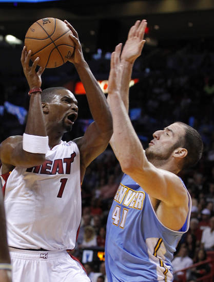 Miami Heat center Chris Bosh (1) goes up for a shot against Denver Nuggets center Kosta Koufos (41) during the first half of an NBA basketball game, Saturday, Nov. 3, 2012 in Miami. (AP Photo/Wilfredo Lee)