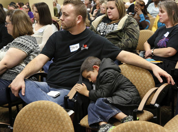 Xizavier (cq) Molden, 5, takes a nap in a chair while his mother, Kathryn Molden, not shown, and other child care providers attend meeting with state regulators.  Seated next to the boy is David Beasley, with Children's Lighthouse 3. About 200  child care providers attended a public forum at Francis Tuttle Technology Center, Reno campus, to  voice their concerns with DHS regulators during a 2-hour session Tuesday afternoon, Nov. 27, 2012.  Photo by Jim Beckel, The Oklahoman