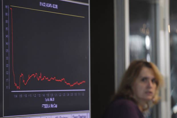 A woman passes a screen   showing a graph of falling stocks at the Athens Stock Exchange, in Athens, on Tuesday, Nov. 1, 2011. Prime Minister George Papandreou's unexpected decision late Monday led to markets plunging Tuesday on fears that Europe's plan to save the euro will unravel.  (AP Photo/Petros Giannakouris) ORG XMIT: ATH103