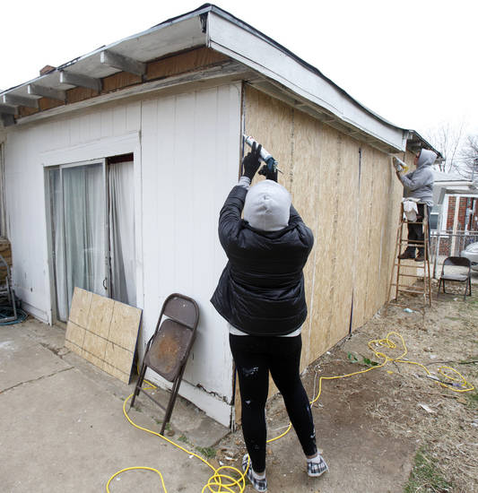 Alaina Houser, left, and Julia Judge seal an exterior wall during a weeklong renovation project in northeast Oklahoma City. By Paul Hellstern, The Oklahoman <strong>PAUL HELLSTERN - Oklahoman</strong>
