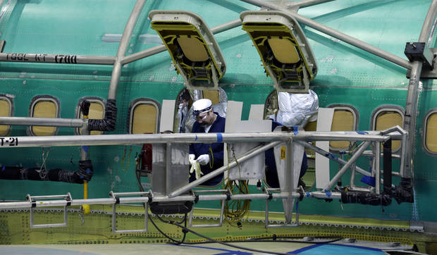 In this Tuesday, Jan. 29, 2013, photo, a Boeing Co. worker is shown through a doorway as he helps build a next-generation 737 airplane, at Boeing's 737 assembly facility in Renton, Wash. Boeing is sticking with plans to speed up production of its 787 and sees no reason to change the lithium-ion battery design at the center of the troubled plane's problems, its CEO said Wednesday, Jan. 30. (AP Photo/Ted S. Warren)