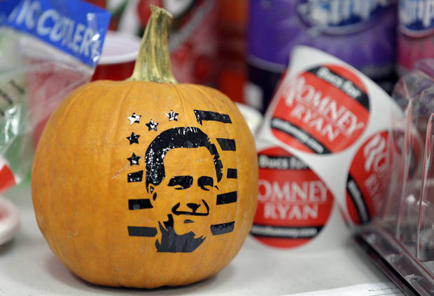 A pumpkin with a sticker depicting Republican presidential candidate, former Massachusetts Gov. Mitt Romney sits on a table at the Romney Ryan Victory Headquarters Monday, Nov. 5, 2012, in Tampa, Fla.. (AP Photo/Chris O'Meara)