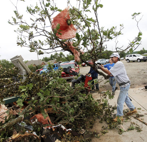 Mark Sarlo tosses a branch onto the pile pile of debris near the street in the Dripping Springs Estates Saturday, May 15, 2010. Saturday hundreds of volunteers went into areas that had been affected by last week's tornadoes to help clear debris. Photo by Doug Hoke, The Oklahoman.