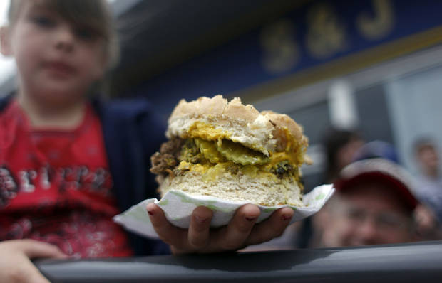 Alaina Weaver holds her portion of the World�s Largest Fried Onion Hamburger during the El Reno Fried Onion Burger Day Festival in 2010. The 24th edition of the festival is Saturday.