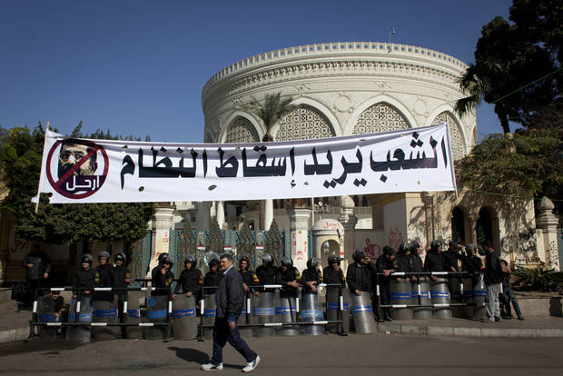 "An Egyptian passes riot policemen guarding a gate of the presidential palace under a banner with a defaced picture of president Mohammed Morsi and Arabic that reads ""the people want to bring down the regime,"" at the protests site, in Cairo, Egypt, Saturday, Dec. 8, 2012. Egypt's military has warned of 'disastrous consequences' if the political crisis gripping the country is not resolved through dialogue. (AP Photo/Nasser Nasser)"