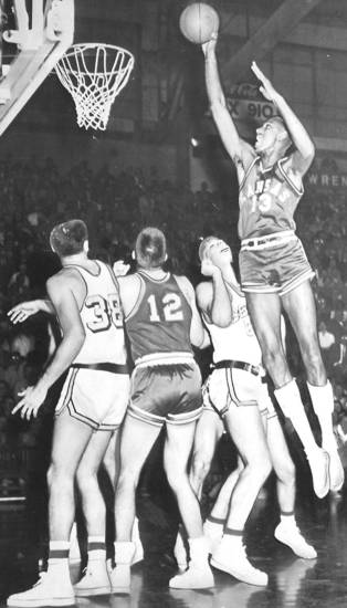 Kansas University basketball center Wilt Chamberlain dunks one for two points early in the game at Berkeley against the University of California. Watching the display, from left: UC forward Larry Friend, Kansas forward Gene Elstun and California center Duane Asplund. The Jayhawks beat the Bears 66-56. (Original photo ran 12/19/56 TIMES)