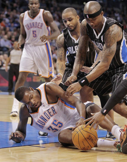 Orlando Magic's Jameer Nelson and Quentin Richardson (right) fight Oklahoma City Thunder's Kevin Durant (35) for a loose ball in the second half as the Oklahoma City Thunder defeat the Orlando Magic 97-89 in NBA basketball at the Chesapeake Energy Arena on Sunday, Dec. 25, 2011, in Oklahoma City, Okla.  Durant had a limp after the pile-up.  Photo by Steve Sisney, The Oklahoman