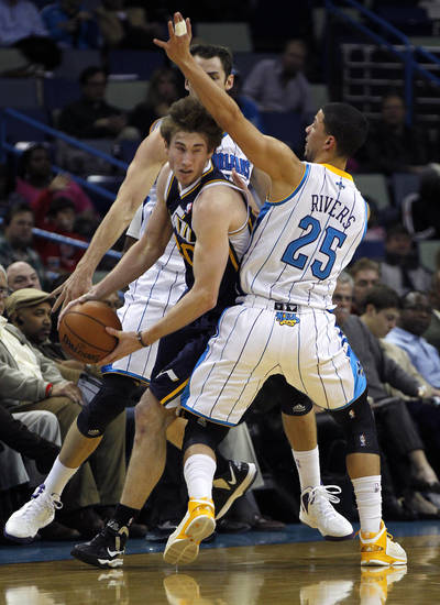Utah Jazz guard Gordon Hayward (20) tries to pass between New Orleans Hornets guard Austin Rivers (25) and forward Jason Smith in the first half of an NBA basketball game in New Orleans, Wednesday, Nov. 28, 2012. (AP Photo/Gerald Herbert)