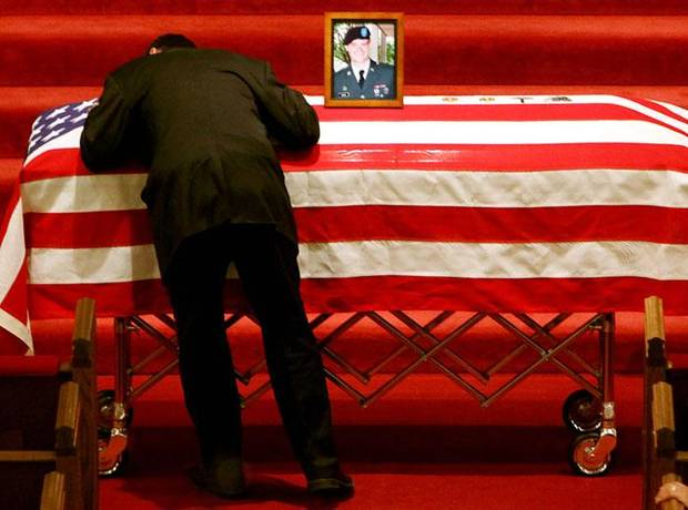 A relative of Gary Moore hugs his casket as services for Cpl. Gary Moore begin at Southwest Baptist Church in Oklahoma City on Tuesday, March 24, 2009. Moore, of Del City, died March 16 when his vehicle hit a roadside bomb in Iraq. He was 25. PHOTO BY JOHN CLANTON, THE OKLAHOMAN