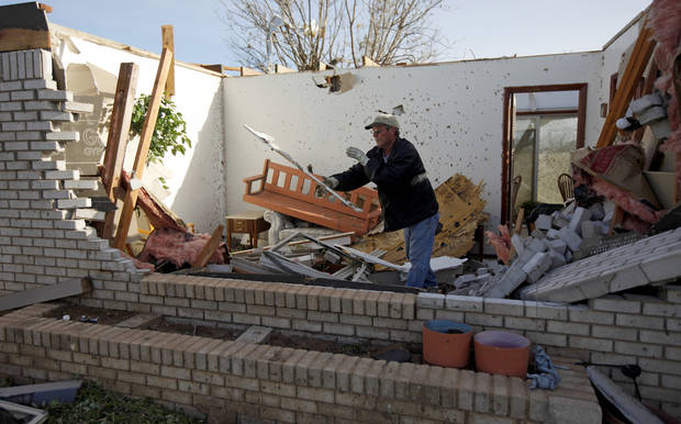 Norman Nelson clears out debris at his mother's home in Woodward, Okla., Sunday, April 15, 2012. A tornado that killed five people struck Woodward, Okla., shortly after midnight on Sunday, April15, 2012. Photo by Bryan Terry, The Oklahoman