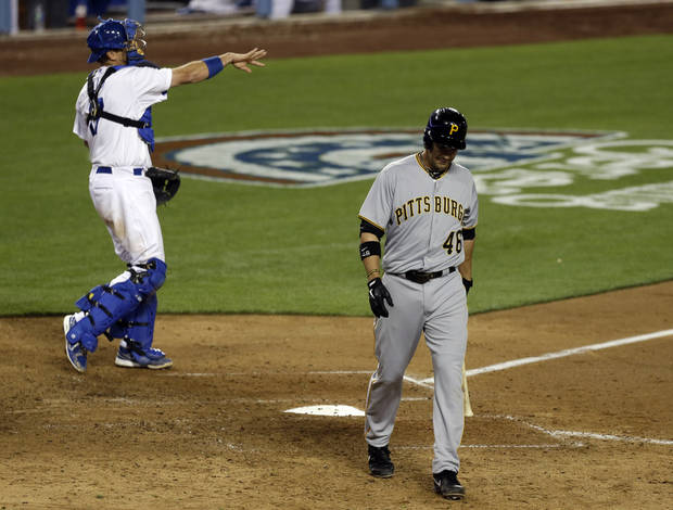 Pittsburgh Pirates' Garrett Jones heads for the dugout after striking out against the Los Angeles Dodgers as catcher Russell Martin throws to the pitcher in the eighth inning of a baseball game in Los Angeles Friday, April 5, 2013. The Dodgers allowed just two Pirates hits and won, 3-0.  (AP Photo/Reed Saxon)