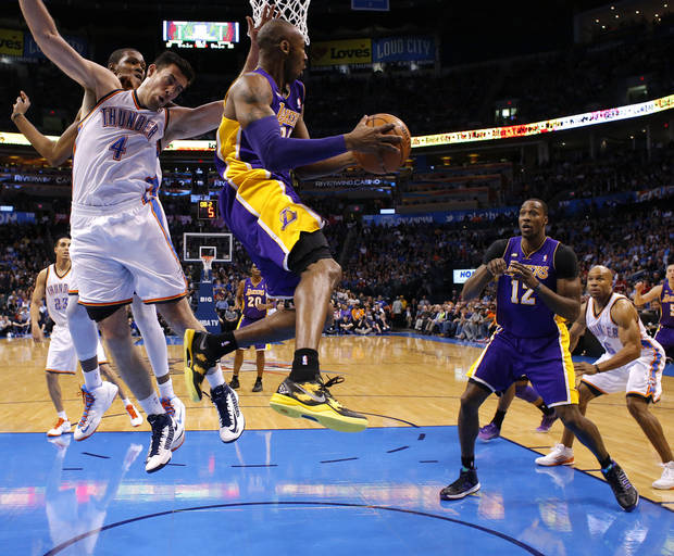 Los Angeles' Kobe Bryant (24) looks to pass to Dwight Howard (12) as he passes by Oklahoma City's Nick Collison (4) during an NBA basketball game between the Oklahoma City Thunder and the Los Angeles Lakers at Chesapeake Energy Arena in Oklahoma City, Tuesday, March. 5, 2013. Photo by Bryan Terry, The Oklahoman