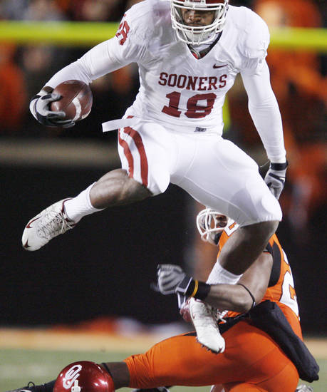OU's Jermaine Gresham jumps over Andre Sexton during the first half of the college football game between the University of Oklahoma Sooners (OU) and Oklahoma State University Cowboys (OSU) at Boone Pickens Stadium on Saturday, Nov. 29, 2008, in Stillwater, Okla. STAFF PHOTO BY BRYAN TERRY