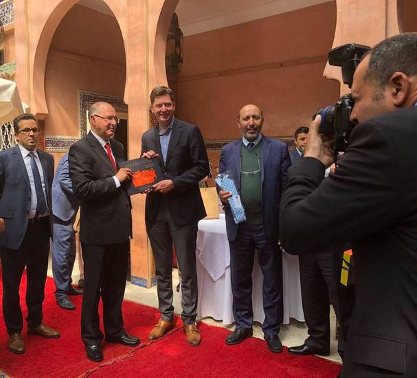Oklahoma City Mayor David Holt, center, met last week with Moroccan officials including Mayor Mohamed Larbi Belcaid, to Holt's left, in Marrakech. The Marrakech mayor is holding an Oklahoma City National Memorial Survivor Tree tie that was a gift from Holt. [Photo courtesy of David Holt]