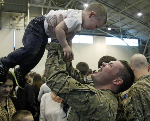 Specialist Willard O'Neal Casey III, right, lifts his 18 month old son Maximus O'Neal Casey, left, into the air, during a welcome home ceremony for 130 returning members of the 45th Infanry Brigade of the Oklahoma National Guard in Oklahoma City, Saturday, March 3, 2012. (AP Photo/Sue Ogrocki) ORG XMIT: OKSO106