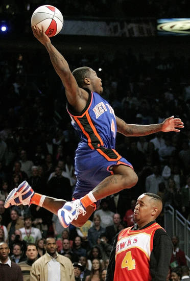 New York's Nate Robinson dunks over Spud Webb for a perfect, 50-point dunk in the second round of the Sprite Rising Stars Slam Dunk Contest during NBA All-Star Saturday Night at the Toyota Center, part of NBA All-Star Weekend in Houston, Texas, Saturday, February 18, 2006. Robinson defeated Philadelphia's Andre Iguodala in overtime. By Nate Billings, The Oklahoman.