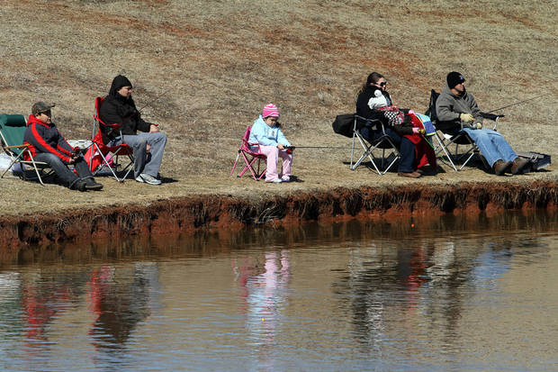 Ready for the chilly weather, participants wait for the next catch during the Trout Fish Out Saturday, March 2, 2013,  morning at the Dale Robertson Activity Center pond in Yukon. PHOTO BY HUGH SCOTT FOR THE OKLAHOMAN