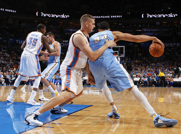 Oklahoma City's Cole Aldrich (45) blocks Denver's JaVale McGee (34) during the NBA preseason basketball game between the Oklahoma City Thunder and the Denver Nuggets at the Chesapeake Energy Arena, Sunday, Oct. 21, 2012. Photo by Garett Fisbeck, The Oklahoman
