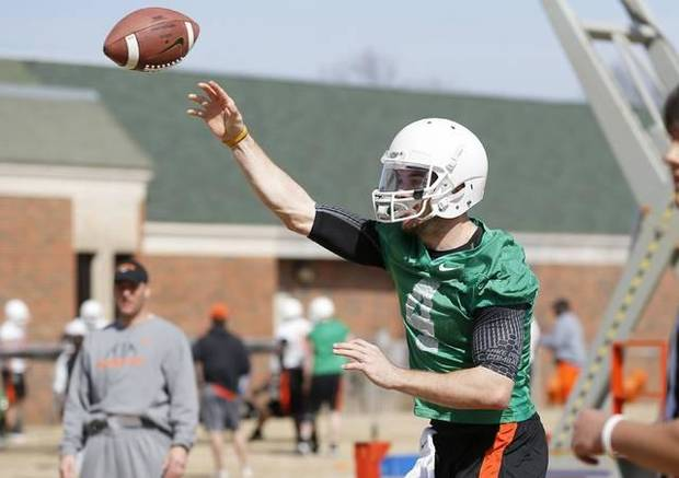 Mike Yurcich looks on as J.W. Walsh throws a pass in practice. / Photo by Bryan Terry