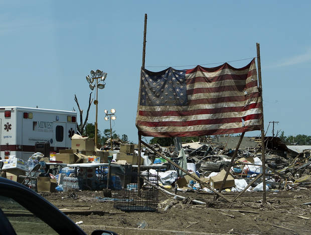 A soiled flag stands next to Plaza Towers Elementary where several students were killed by Monday's tornado on Wednesday, May 22, 2013 in Moore, Okla. Photo by Steve Sisney, The Oklahoman