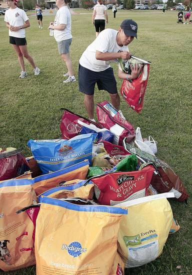 Paul Nguyen adds to the collection of dog food for dog rescue groups.