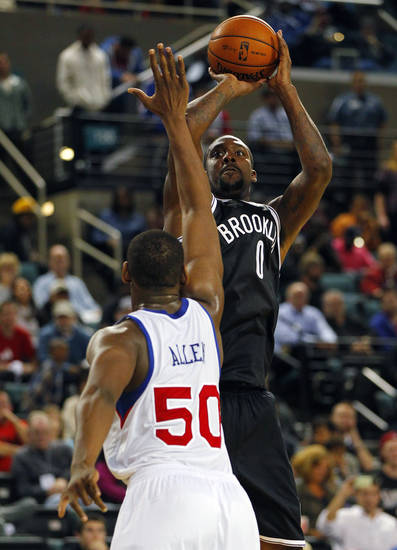 Brooklyn Nets' Andray Blatche (0) takes a jump shot as Philadelphia 76ers' Lavoy Allen (50) defends in an NBA preseason basketball game in Atlantic City , N.J., Saturday, Oct. 13, 2012. The Nets won 108-105 in overtime. (AP Photo/Rich Schultz)